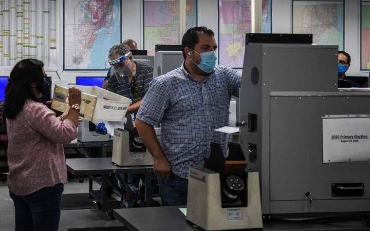 Employees of Miami-Dade Elections Department scan the votes for counting during Florida Primary Election amid the coronavirus pandemic, at Miami-Dade Elections Department in Miami, Florida on August 18, 2020.