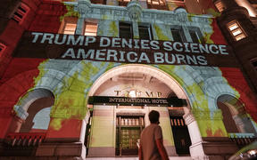 Activists project flames and commentary on the side of the Trump International Hotel in protest of President Donald Trump's response to science and climate change.