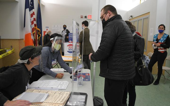 A man wearing a face mask registers for the voting at a pooling station during the Presidential election, in New York.
