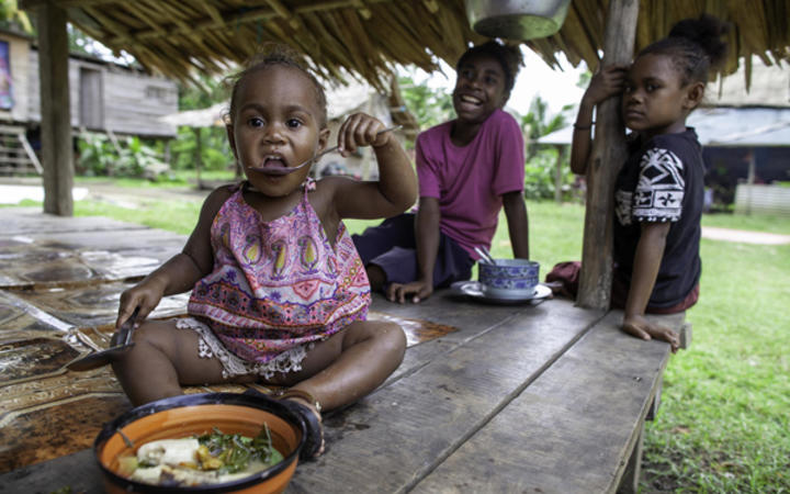 A girl eats vegetable broth in Guadalcanal, Solomon Islands. 25 August, 2019