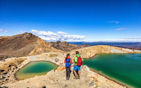 New Zealand popular tourist hiking hike in Tongariro Alpine Crossing National Park. Tramping trampers couple hikers walking on famous destination in NZ.