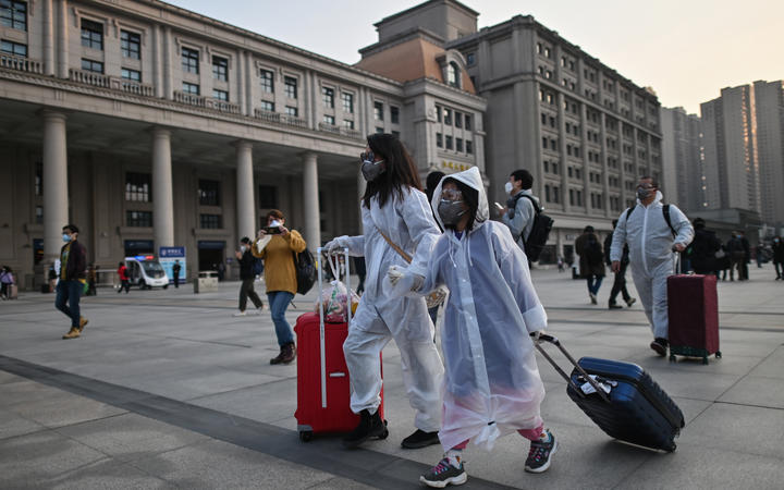 People wearing protective clothing and masks arrive at Hankou Railway Station to board one of the first trains to leave Wuhan after an outbound travel ban was lifted on April 8, 2020.