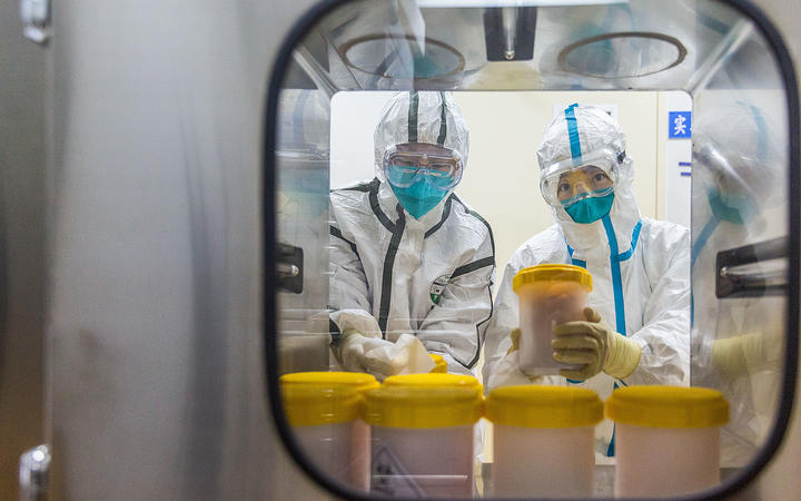 Staff members receive the novel coronavirus strain transported to a laboratory of Chinese Center for Disease Control and Prevention, in Beijing, on February 25, 2020.
