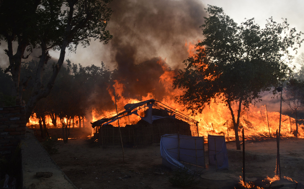 Former homes of Indian members of a sect burn following clashes with police during an eviction at the Jawahar Bagh park in Mathura on June 2, 2016.