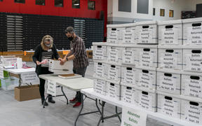 Poll workers check in a box of absentee ballots in Sun Prairie, Wisconsin, on 3 November 2020.