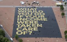 "Plainpalais place in Geneva shows a giant poster reading ""What would you do if your income was taken care of?""."