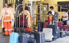 Local officials in protective gear help with baggage as Australian residents arrive at a hotel in Adelaide for mandatory 14-day quarantine after returning on a repatriation flight on 21 April 2020.