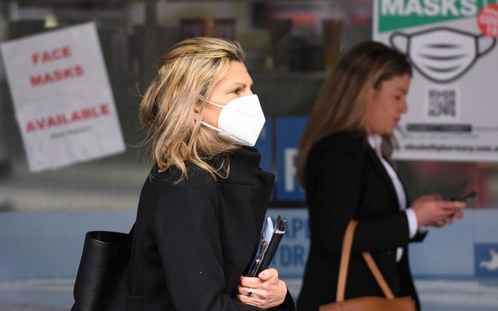 People wearing face masks walk past a sign advertising masks in Melbourne on July 20, 2020.