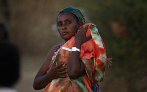 An Ethiopian refugee who fled fighting in Tigray province carries her baby as she walks at the Um Rakuba camp in Sudan's eastern Gedaref province, on November 21, 2020.