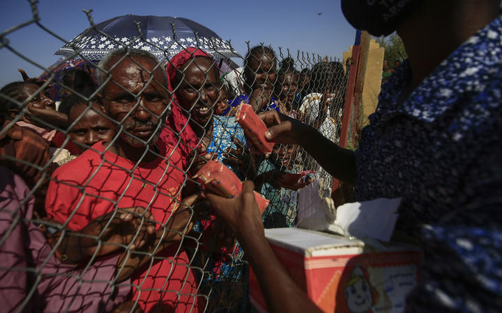 Ethiopian refugees who fled fighting in the Tigray Region receive snacks at the Village 8 border reception center in Sudan's eastern Gedaref State, on November 20, 2020.