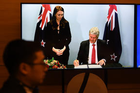Prime Minister Jacinda Ardern looks on as Minister of Trade Damien O'Connor signs the RCEP agreement at the ASEAN summit that was held online in Hanoi on November 15, 2020.