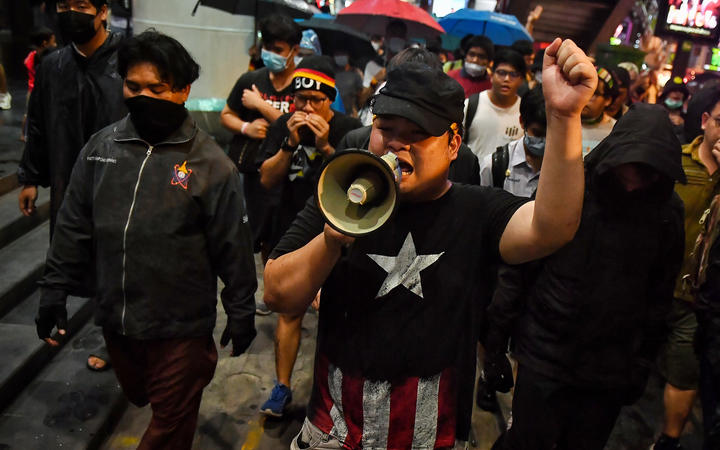 Pro-democracy activist Parit Chiwarak (centre) uses a loudspeaker as he walks with others towards the police headquarters in Bangkok on October 13, 2020.
