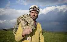 Cave explorer Francisco Sauro wearing a safety helmet with a headlamp. He is carrying a length of rope and is dressed in overalls