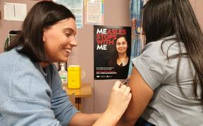Nurse Laura Williams gives a Māngere College student a measles vaccination.