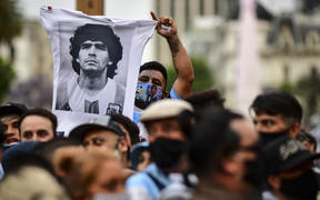 A man waves t-shirt with a picture of Diego Maradona as fans wait to enter Government House to pay tribute to the late football legend, Buenos Aires, 26 November.