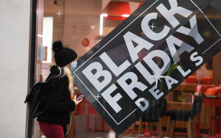 A pedestrian wearing a mask because of the novel coronavirus pandemic walks past a shop advertising Black Friday sales on Oxford Street in London on November 26, 2020.