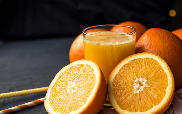 Fresh orange juice and fresh fruit oranges on a black background