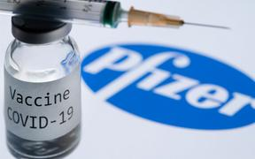 "File: This illustration picture taken in Paris on November 23, 2020 shows a syringe and a bottle reading ""Covid-19 Vaccine"" next to the Pfizer company logo."
