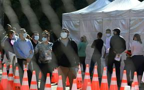 People wait in long lines for covid tests at a walk-up Covid-19 testing site in San Fernando, California.