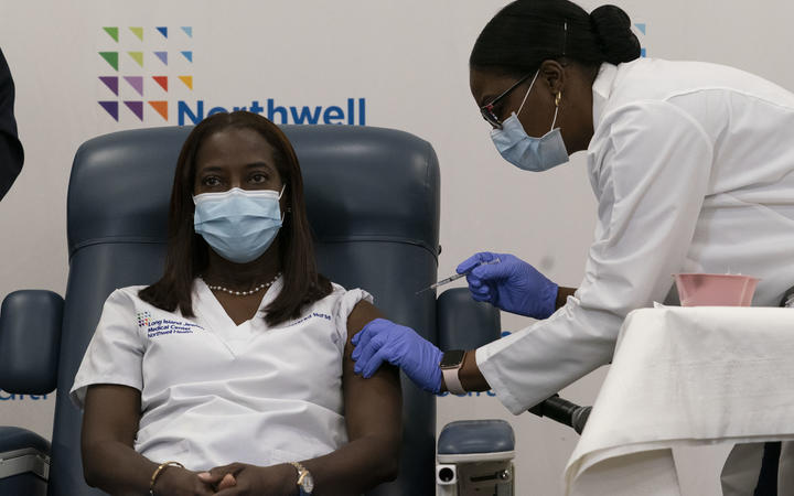 Sandra Lindsay, left, a nurse at Long Island Jewish Medical Center, is inoculated with the Covid-19 vaccine by Dr. Michelle Chester, December 14, 2020 in the Queens borough of New York City.