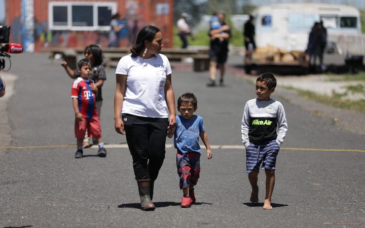 SOUL co-spokesperson Pania Newton holds the hand of a child while walking with others.