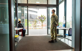 A security guard and soldier guarding an entrance to the M-Social Hotel, which is being used as a managed isolation facility, in Auckland.