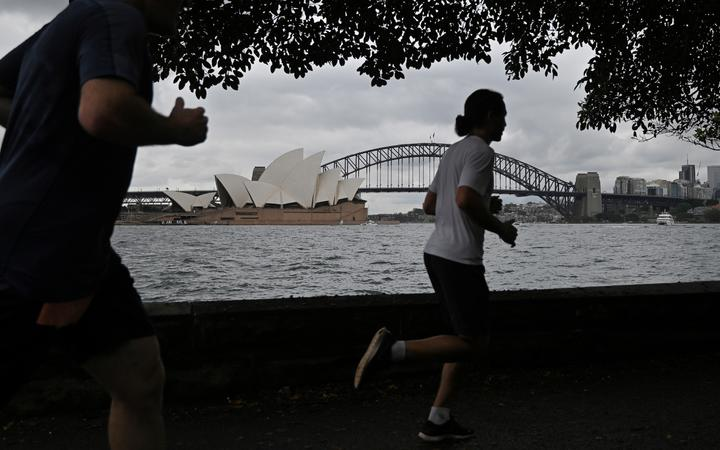 People run before the Opera House and Harbour Bridge in Sydney on December 20, 2020, after authorities introduced a fresh round of restrictions.