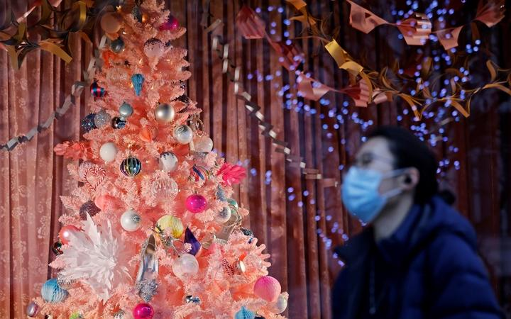 A pedestrian wearing a face mask or covering due to the COVID-19 pandemic, walks past a Christmas-themed display in a shop window on Oxford Street in central London on December 22, 2020.
