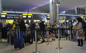 Passengers wearing masks queue at Heathrow Airport in west London on December 21, 2020.