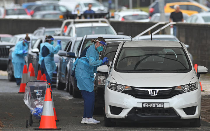 Health workers perform Covid-19 tests at a drive-through testing centre at Bondi Beach in Sydney on December 20, 2020.