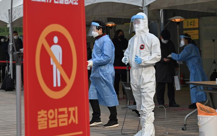 A medical staff member wearing protective gear prepares to test visitors for Covid-19 at a temporary testing station in Seoul on December 23, 2020.
