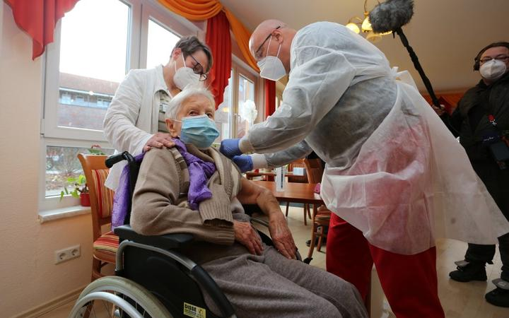 Edith Kwoizalla, 101 years old, receives the first vaccination against the novel coronavirus COVID-19 by Pfizer and BioNTech from Doctor  Bernhard Ellendt (R) in a senior care facility in Halberstadt (Seniorenzentrum Krueger), central northern Germany, on December 26, 2020.