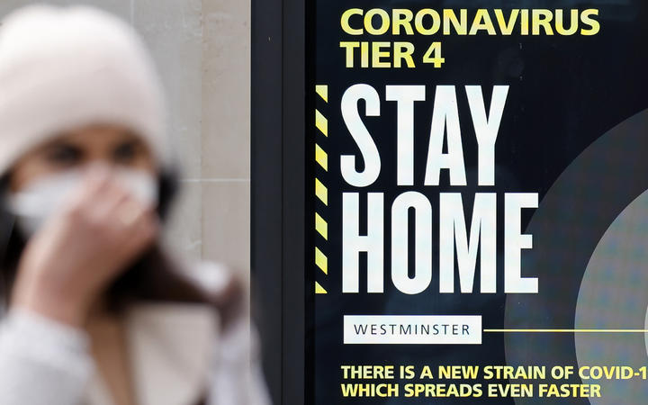 A pedestrian wearing a mask walks past a sign alerting people that Covid-19 cases are very high in London on December 23, 2020.