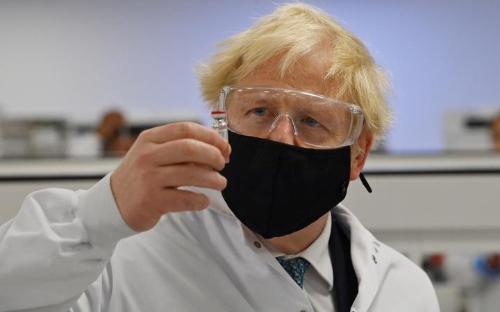 Britain's Prime Minister Boris Johnson poses for a photograph with a vial of the AstraZeneca/Oxford University COVID-19 candidate vaccine, known as AZD1222, at Wockhardt's pharmaceutical manufacturing facility in Wrexham, north Wales, on November 30, 2020.