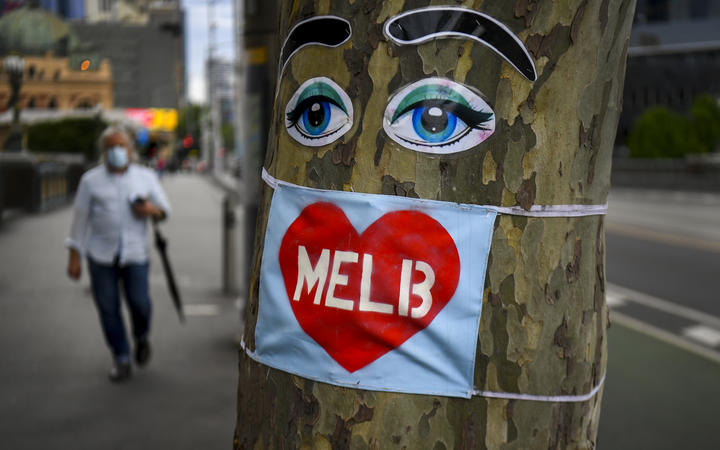 File photo: People walk past a tree decorated with eyes and a face mask in Melbourne's central business district  in October