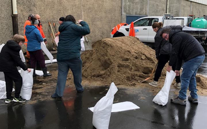 People fill bags at one of Dunedin's sandbagging stations