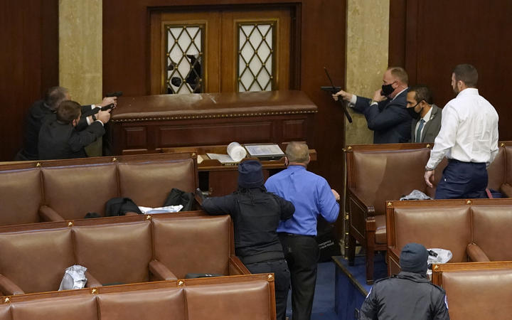 US Capitol police officers point their guns at a door that was vandalised in the House Chamber during a joint session of Congress on January 06, 2021 in Washington, DC.