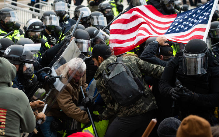 Supporters of US President Donald Trump fight with riot police outside the Capitol building on 6 January 2021 in Washington DC.