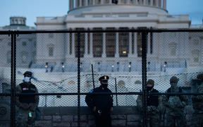 A Capitol Police officer stands with members of the National Guard behind a crowd control fence surrounding Capitol Hill a day after a pro-Trump mob broke into the US Capitol on January 7, 2021, in Washington, DC.