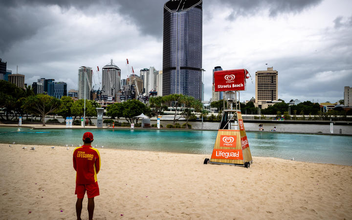 A lifeguard stands watch over a deserted South Bank beach on the first day of a snap lockdown in Brisbane on 9 January