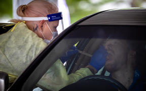 A healthcare worker tests a person at a drive-through Covid-19 testing clinic on the first day of a snap lockdown at Murarrie in Brisbane on January 9.