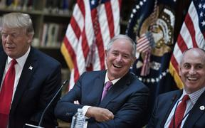 Stephen A. Schwarzman (C), CEO of the Blackstone Group, and Chris Liddell (R), White House Director of Strategic Initiatives, and US President Donald Trump (L) and others in the  White House campus April 11, 2017 in Washington, DC.