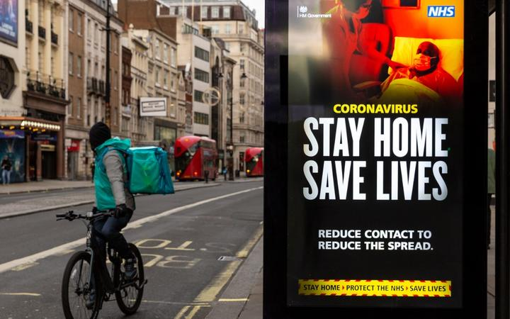 A delivery man on his bicycle is seen riding by the NHS 'Stay Home' poster as the UK's government introduced strict Coronavirus restrictions earlier this month due to sharp increase in numbers of Covid-19 cases in UK o)