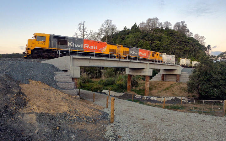 A freight train crosses the new Bridge 100, on Helleyer road, 15km from Helensville.  The new bridges have a concrete ballast tray deck which requires less maintenance than the old bridges, and can carry up to 25-tonne axle loads.
