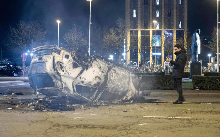 A burned car in front of Eindhoven central train station after the anti-lockdown protest.