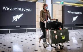 A passenger wearing a face mask arrives from New Zealand at Sydney International Airport on October 16, 2020, after Australia's border rules were relaxed under a new one-way trans-Tasman travel agreement.