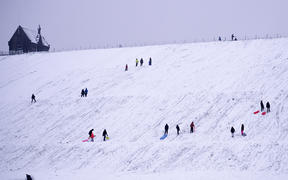 People sledge down a hillside at  Butterley Reservoir in Marsden, northern England on January 14, 2021 as heavy snow fell on parts of the UK
