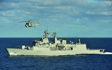 The HMNZS Te Kaha out at sea with a helicopter flying above