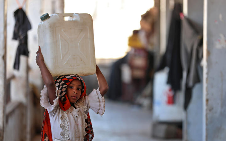 A girl carries a water container on her head at a school building for displaced Yemenis in the town of al-Turba in Taez on February 4, 2021.