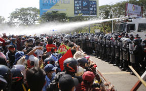 Police fire water cannon at protesters as they demonstrate against the 1 February   military coup in the capital Naypyidaw, 9 February, 2021.